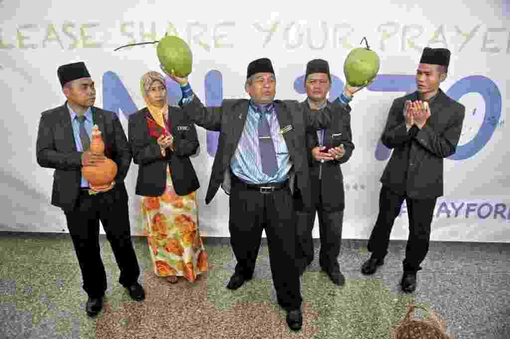 12.mar.2014 - O xamã Ibrahim Mat Zin (ao centro), bastante conhecido na Malásia, segura dois cocos no aeroporto internacional de Kuala Lumpur. Junto com seus assistentes, o xamã se ofereceu para localizar o avião da Malaysia Airlines que está desaparecido desde sábado (8), por meio de rezas e atividades espirituais - Mohd Rasfan/AFP