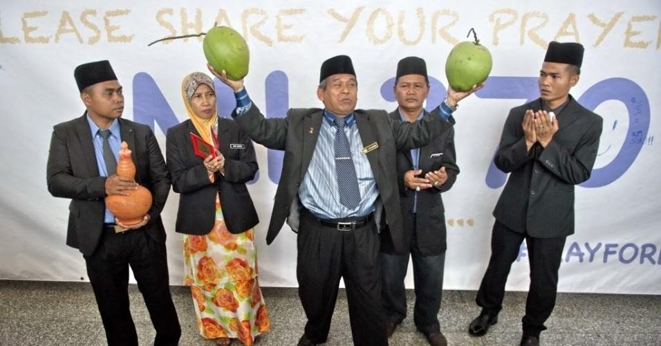 12.mar.2014 - O xamã Ibrahim Mat Zin (ao centro), bastante conhecido na Malásia, segura dois cocos no aeroporto internacional de Kuala Lumpur. Junto com seus assistentes, o xamã se ofereceu para localizar o avião da Malaysia Airlines que está desaparecido desde sábado (8), por meio de rezas e atividades espirituais
