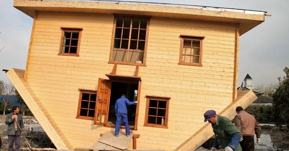 13.mar.2014 - Funcionários trabalham na construção de casa de cabeça para baixo em Fengting, em Xangai, leste da China. A casa invertida tem dois andares e três cômodos com móveis colocados de cabeça para baixo