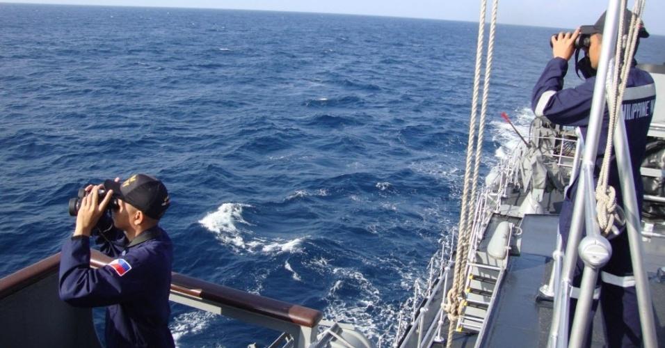 14.mar.2014 - Membros da Marinha das Filipinas participam de busca do avião da Malaysia Airlines no mar das Filipinas, em imagem feita no dia 10 de março e divulgada nesta sexta-feira (14)
