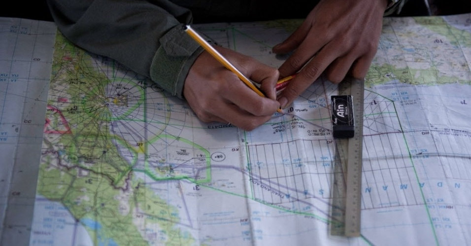 14.mar.2014 - Oficial da Força Aérea da Malásia marca locais em mapa ao sobrevoar o estreito de Malacca, no oceano Índico, durante operação de busca de avião da Malaysia Airlines desaparecido desde o último sábado (8)