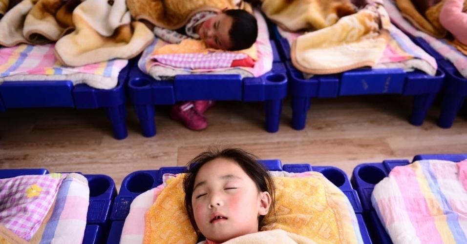 14.mar.2014 - Uma menina tira um cochilo no Jardim de Infância da escola pública de Tianjun County, na China, nesta sexta-feira (14)