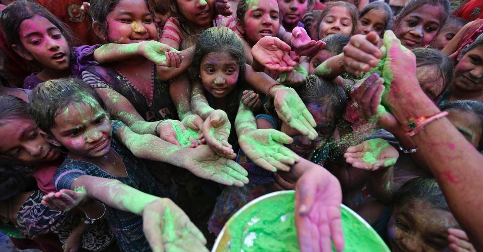 15.mar.2014 - Alunos estendem as mãos para receber o pó colorido de professor, durante as celebrações do Holi em uma escola na cidade indiana de Ahmedabad. O Holi, também conhecido como o festival das cores, anuncia o início da primavera e é comemorado por toda a Índia