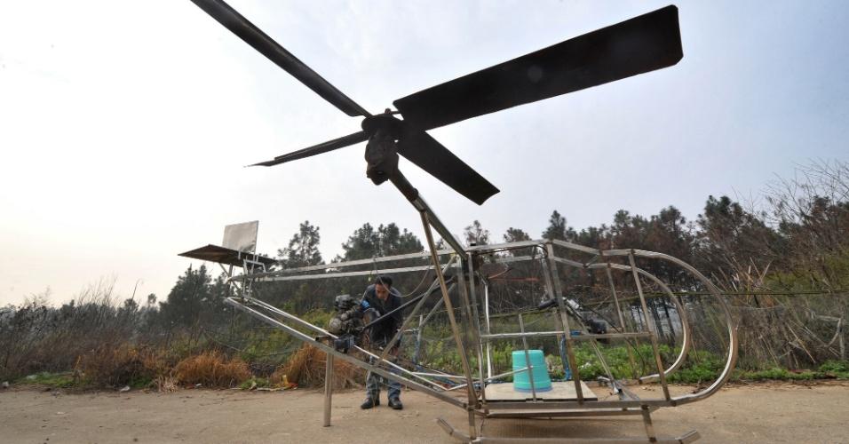 14.mar.2014 - O fazendeiro Li Housheng examina o motor de seu helicóptero no vilarejo Ganzhou, na Província de Hunan, centro da China. Li Housheng, 52, começou a fazer a aeronave em agosto de 2013. Ela usa um motor de motocicleta e sua estrutura é feita de ferro e tubos de aço inoxidável. Cada rotor é uma simples solda de quatro placas de aço. O sistema de controle do helicóptero, que inclui acelerador, embreagem e manche, também vem de partes de motocicleta. O helicóptero completou um teste de voo planando a 40 centímetros do solo, de acordo com Li. O agricultor agora tenta fazê-lo voar mais alto. A foto foi disponibilizada neste domingo (16)