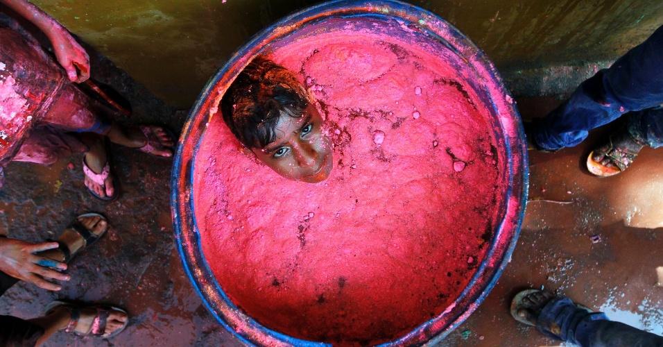 16.mar.2014 - Garoto mergulha em barril de plástico com água colorida  durante as comemorações do Festival Holi, em Chennai, no sul da Índia. Também conhecido como Festival das Cores, o Holi comemora a chegada da primavera e é celebrado em todo o país