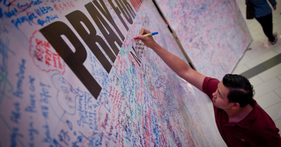 16.mar.2014 - Homem escreve mensagem para passageiros do voo da companhia Malaysia Airlines, desaparecido desde o dia 8 de março. O painel de mensagens está no aeroporto internacional de Kuala Lumpur, na Malásia