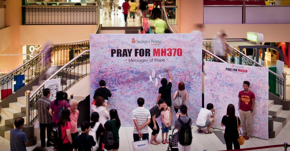 16.mar.2014 - Parentes e amigos escrevem mensagem para passageiros do voo da companhia Malaysia Airlines, desaparecido desde o dia 8 de março. O painel está no aeroporto internacional de Kuala Lumpur, na Malásia