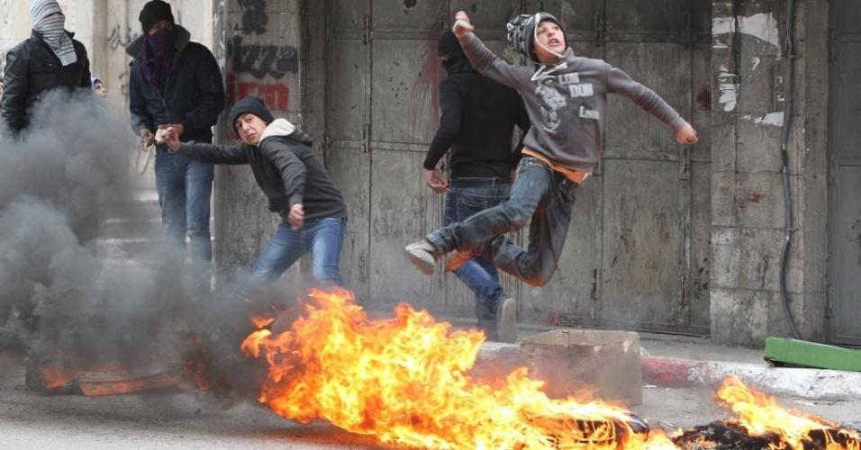 17.mar.2014 - Dois meninos palestinos atiram pedras durante um confronto com as forças de segurança de Israel, na cidade de Hebron