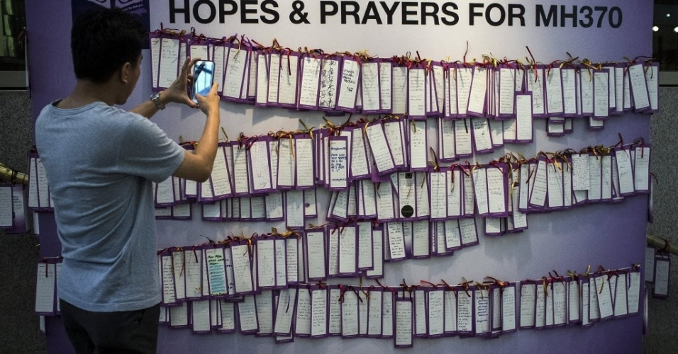17.mar.2014 - Homem fotografa mensagens de apoio aos passageiros do voo MH370 da Malaysia Airlines, que está desaparecido desde 8 de março, em um centro comercial de Kuala Lumpur, na Malásia. 26 países participam da busca do avião, que desapareceu com 239 pessoas a bordo