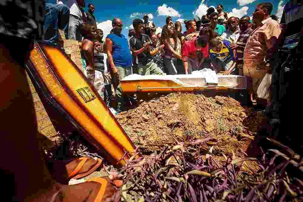 17.mar.2014 - Parentes e amigos se reúnem no cemitério do Irajá, na zona norte do Rio de Janeiro, para o sepultamento de Claudia Silva Ferreira, 38, nesta segunda-feira (17). A moradora do morro da Congonha, em Madureira, foi encontrada baleada pelos policiais no alto da favela, depois de um tiroteio. Dois subtenentes e um soldado do batalhão da PM de Rocha Miranda resolveram colocá-la no porta-malas do carro da polícia. No trajeto para o hospital, o porta-malas se abriu e ela foi projetada para fora do carro, sendo arrastada pelo veículo - Daniel Marenco/Folhapress