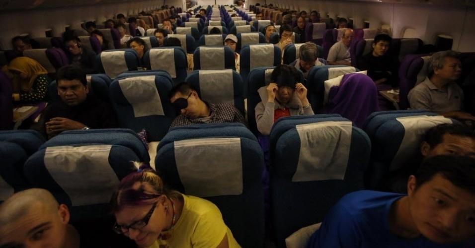 17.mar.2014 - Passageiros a bordo do voo MH318, da Malaysia Airlines, que saiu de Kuala Lumpur, na Malásia, em direção a Pequim, na China. A companhia aérea substituiu o número do voo MH370 por MH378 em respeito aos passageiros e à tripulação a bordo da aeronave desaparecida desde o dia 8 de março