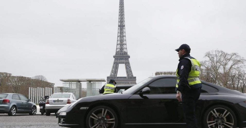 17.mar.2014 - Policiais fazem controle de carros em frente a torre Eiffel, em Paris, França. A cidade recorreu a medidas drásticas para conter a alta dos níveis de poluição fazendo um rodízio de carros. Cerca de 700 policiais foram mobilizados para fazer o controle dos automóveis