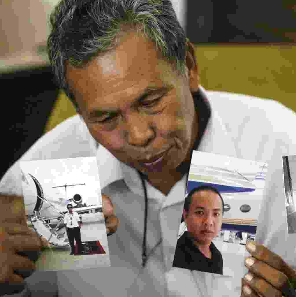 17.mar.2014 - Selamat Omar mostra fotografias de seu filho, Mohd Khairul Amri Selamat, um engenheiro de aviação que estava a bordo do voo MH370 da Malaysia Airlines, desaparecido desde o dia 8 de março. A presença do engenheiro no avião está sendo investigada devido à suspeita de que um dos sistemas de localização da aeronave tenha sido desligado - Ahmad Yusni/Efe