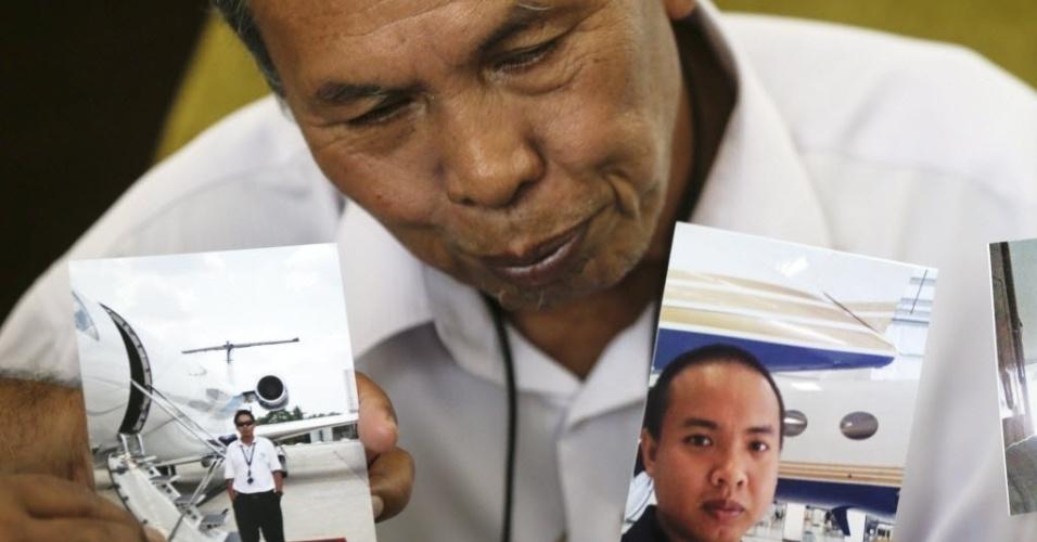 17.mar.2014 - Selamat Omar mostra fotografias de seu filho, Mohd Khairul Amri Selamat, um engenheiro de aviação que estava a bordo do voo MH370 da Malaysia Airlines, desaparecido desde o dia 8 de março. A presença do engenheiro no avião está sendo investigada devido à suspeita de que um dos sistemas de localização da aeronave tenha sido desligado