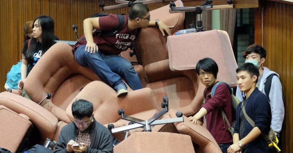 18.mar.2014 - Ativistas anti-China usam cadeiras para bloquear a entrada do Parlamento de Taiwan, em Taipé, que se prepara para assinar acordos comerciais com a China