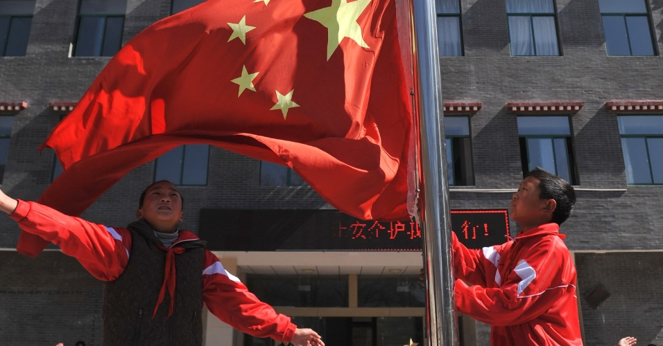 18.mar.2014 - Estudantes participam de uma cerimônia de hasteamento da bandeira em uma escola primária de Yunnan, no sudoeste da China. O colégio público tem 1.210 alunos, sendo a maior parte tibetanos