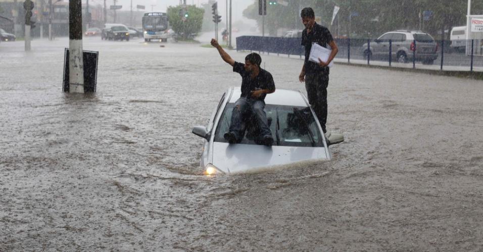 18.mar.2014 - Homens sobem em carro durante alagamento na avenida Roque Petroni Júnior, na zona sul de são Paulo. Diversos pontos da cidade ficaram alagados no início da tarde desta terça-feira (18)