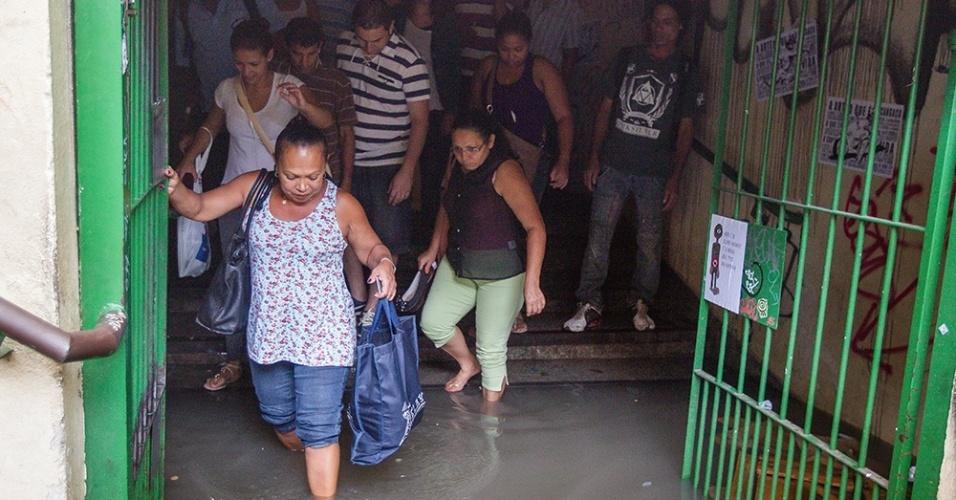 18.mar.2014 - Túnel que liga a rua William Speers ao terminal de ônibus da Lapa, na zona oeste de São Paulo, ficou alagado, obrigando passageiros a colocaram os pés na água para terem acesso ao transporte coletivo, nesta terça-feira (18). Segundo a Defesa Civil da cidade, ao menos 100 atendimentos foram feitos pelas equipes da prefeitura por causa das chuvas, que incluem 17 casos de quedas de árvore. Até as 19h47, havia 54 semáforos apagados e 11 em amarelo intermitente na cidade, totalizando 65 ocorrências ativas. De acordo com a CET (Companhia de Engenharia de Tráfego de São Paulo), os números estão dentro da média de um dia sem chuvas, quando são registradas, em média, de 65 a 70 ocorrências semafóricas. Partes do bairro da Pombeia, na zona oeste da capital paulista, ficaram sem energia elétrica por pelo menos quatro horas. Além disso, as fortes chuvas causaram colisões entre veículos em ruas alagadas e paralisação de trens da linha 8-Diamante CPTM (Companhia Paulista de Trens Metropolitanos)