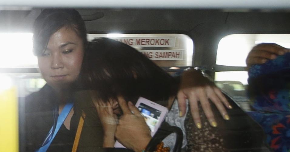10.mar.2014 - Uma parente de passageiro que estava a bordo do voo MH370 da Malaysia Airlines, que está desaparecido, é confortada por uma funcionária do aeroporto enquanto ela protege o rosto de jornalistas, no aeroporto internacional de Kuala Lumput, em Sepang