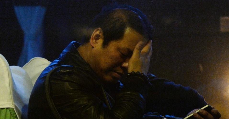 11.mar.2014 - Parente de passageiros do voo MH370 da Malaysia Airlines, que está desaparecido, espera em um ônibus após pegar seu visto malaio no hotel Metro Park Lido, em Pequim, na China