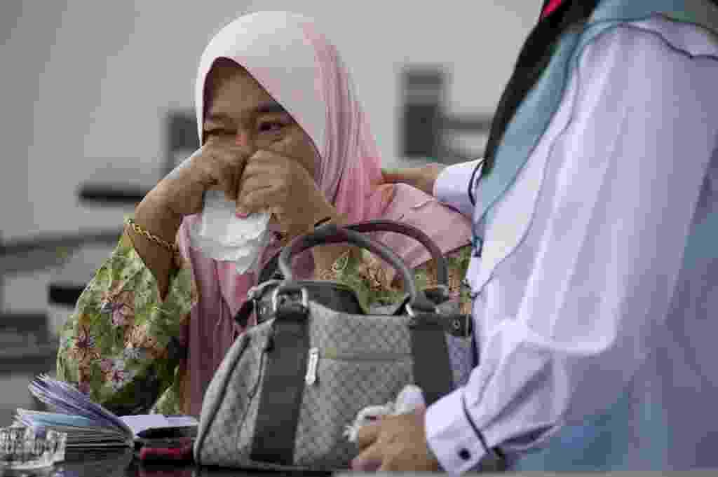 11.mar.2014 - Uma parente de um dos passageiros que estava a bordo do voo MH370 da Malaysia Airlines, que está desaparecido, chora enquanto espera novas informações em um hotel em Putrajaya, na Malásia - Mohd Rasfan/AFP
