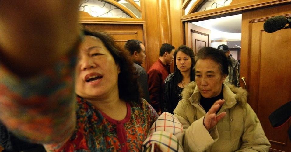 14.mar.2014 - Mulher tenta tapar câmera de fotógrafo na saída de uma reunião entre familiares dos passageiros do voo MH370 da Malaysia Airlines e funcionários da companhia, em hotel em Pequim, na China
