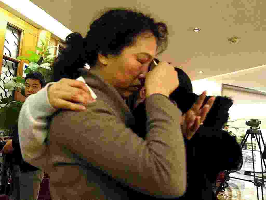 14.mar.2014 - Uma mulher chora enquanto abraça parente de passageiro do voo da Malaysia Airlines que está desaparecido, após receber novas informações sobre o avião, em Pequim, na China - Goh Chai Hin/AFP