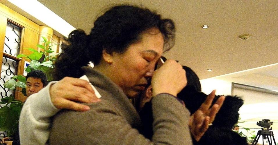 14.mar.2014 - Uma mulher chora enquanto abraça parente de passageiro do voo da Malaysia Airlines que está desaparecido, após receber novas informações sobre o avião, em Pequim, na China