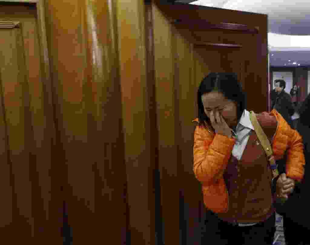 14.mar.2014 - Uma mulher chora enquanto sai de uma sala cheia de parentes e amigos dos passageiros que estavam a bordo do voo MH370 da Malaysia Airlines, que está desaparecido, em um hotel em Pequim, na China - Kim Kyung-Hoon/Reuters