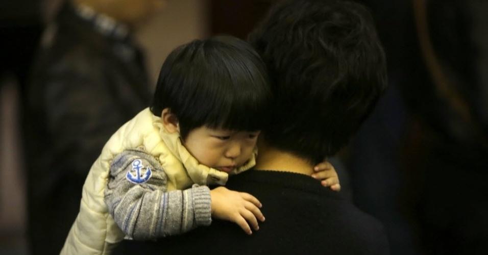 16.mar.2014 - Criança é carregada por parente de passageiro do voo MH370 da Malaysia Airlines durante uma reunião com funcionários da companhia aérea em hotel de Pequim, na China