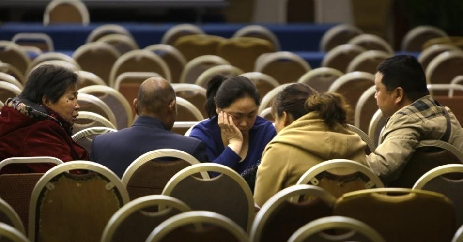 16.mar.2014 - Parentes de passageiros que estavam a bordo do voo MH370 da Malaysia Airlines, que está desaparecido, conversam após uma reunião com representantes da companhia aérea, no hotel Lido, em Pequim, na China