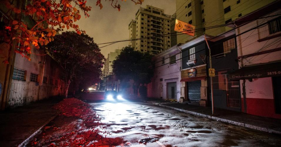 18.mar.2014 - Carro passa pela rua Raul Pompeia, no bairro Pompeia, zona oeste de São Paulo, que ficou às escuras após uma forte tempestade atingir a cidade na terça-feira (18). Moradores reclamam que estão sem energia elétrica há mais de 12 horas