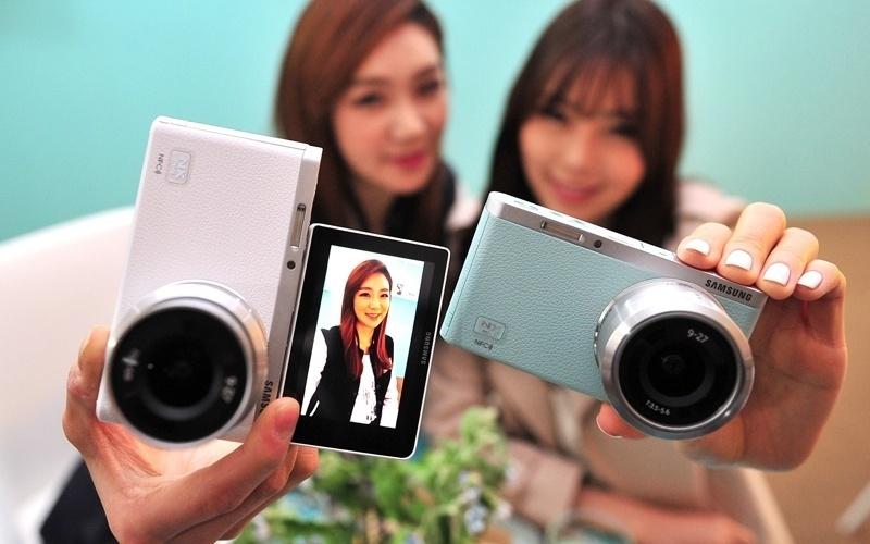 19.mar.2014 - A Samsung anunciou o lançamento da câmera NX Mini, com 20,5 megapixels, flash e lentes intercambiáveis. O principal destaque do acessório é a tela LCD de 3 polegadas, que gira 180º, facilitando assim o registro de selfies (autorretratos). Ela grava vídeos, tem diversos filtros e conexão Wi-Fi e NFC (de troca de arquivos via aproximação de aparelhos). Os preços vão de US$ 449 (cerca de R$ 1.051; kit com lente 9mm f/3.5) a US$ 549 (R$ 1.285; kit com lente 9-27mm)