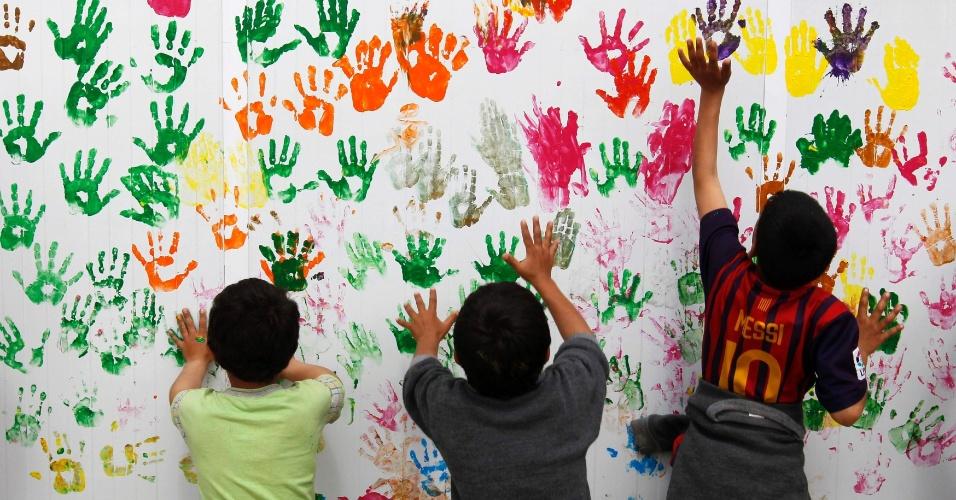 19.mar.2014 - Crianças sírias realizam uma atividade de pintura na escola no acampamento de refugiados Al Zaatari na cidade jordaniana de Mafraq