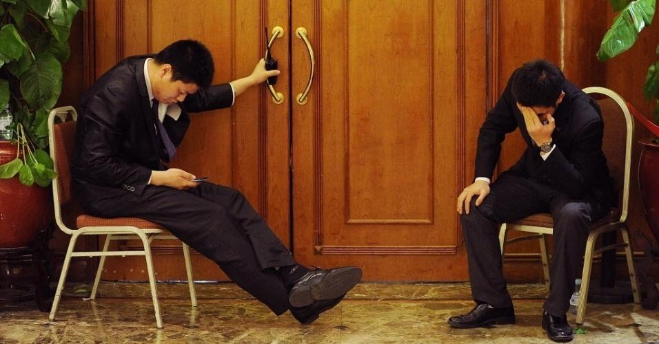 19.mar.2014 - Dois seguranças sentam na entrada do lounge de um hotel onde parentes de passageiros do voo MH370 da Malaysia Airlines, que está desaparecido estão reunidos em Pequim