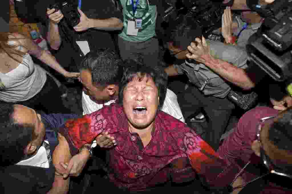 19.mar.2014 - Familiar de passageiro do MH370 , da Malaysian Airlines, que desapareceu no dia 8 de março, chora em frente a jornalistas na sala de imprensa do aeroporto de Kuala Lumpur. Vários familiares de passageiros chineses que estavam a bordo do avião desaparecido  invadiram a sala onde autoridades malaias faziam um pronunciamento a jornalistas - Azhar Rahim/EFE