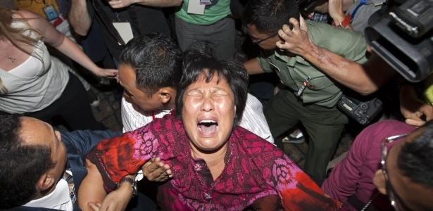 Familiar de passageiro do avião que desapareceu chora na sala de imprensa do aeroporto de Kuala Lumpur - Azhar Rahim/EFE
