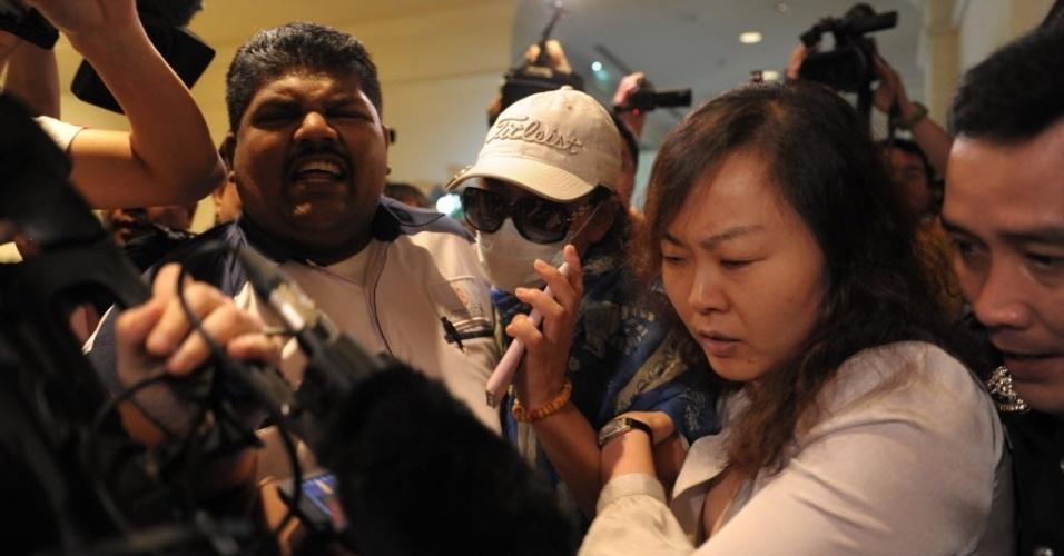 19.mar.2014 - Familiares de passageiros chineses do voo MH370 da Malaysia Airlines são impedidos pela polícia de entrar na sala de imprensa de um hotel próximo ao aeroporto internacional de Kuala Lumpur, na Malásia, onde nesta quarta-feira (19) aconteceu uma entrevista coletiva sobre o voo desaparecido em 8 de março
