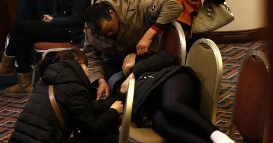 14.mar.2014 - Parente de passageiro do voo MH370, que está desaparecido desde 8 de março, descansa em cadeiras em sala de hotel de Pequim, na China, enquanto aguarda notícias sobre o paradeiro da aeronave