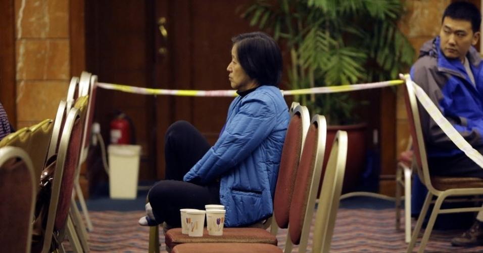 19.mar.2014 - Parente de passageiros do voo MH370 da Malaysia Airlines aguarda notícias do voo desaparecido no dia 8 de março, em sala de hotel de Pequim, na China