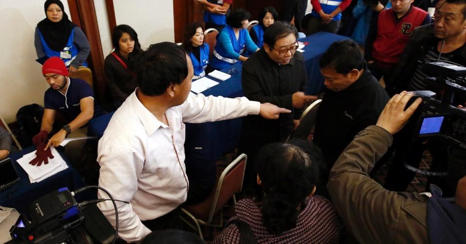19.mar.2014 - Parentes de passageiros do voo MH370, desaparecido desde o dia 8, reclamam com um funcionário da Malaysia Airlines após entrevista coletiva da empresa para os membros das famílias em um hotel em Pequim, na China