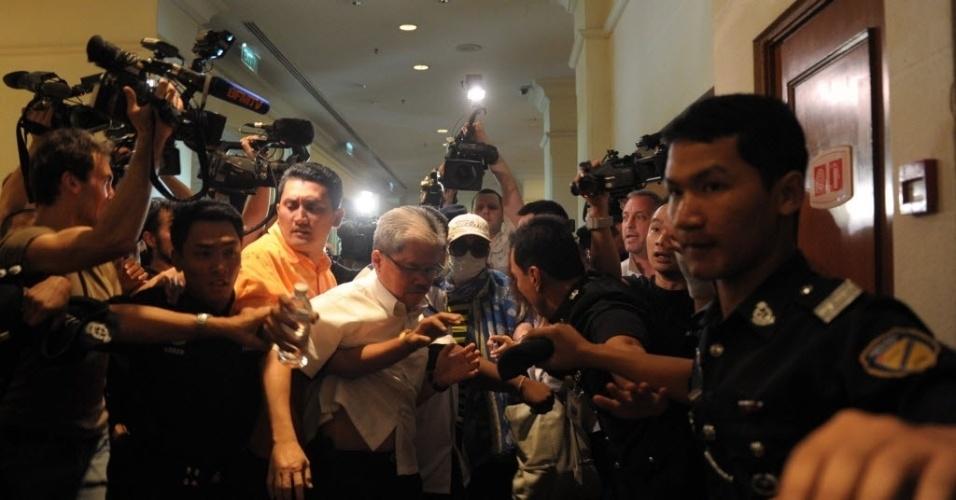 19.mar.2014 - Um parente de um dos passageiros do voo MH370 da Malaysia Airlines, que está desaparecido, é escoltado por um policial malaio para fora do centro de mídia, antes do início de uma conferência de imprensa em um hotel próximo ao aeroporto internacional de Kuala Lumpur, na Malásia, em Sepang