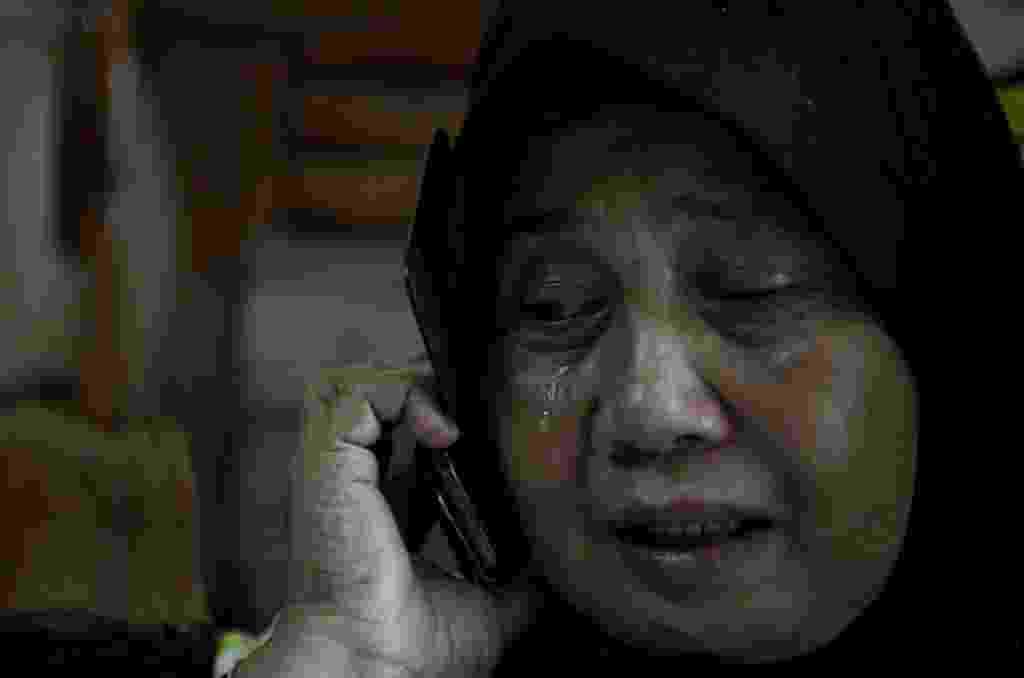 8.mar.2014 - Um parente de Norliakmar Hamid e Razahan Zamani, passageiros do voo da Malaysia Airlines que está desaparecido, chora enquanto fala ao telefone em Kuala Lumpur, na Malásia - Mohd Rasfan/AFP