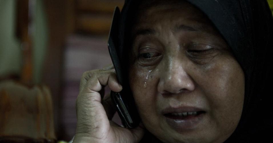 8.mar.2014 - Um parente de Norliakmar Hamid e Razahan Zamani, passageiros do voo da Malaysia Airlines que está desaparecido, chora enquanto fala ao telefone em Kuala Lumpur, na Malásia