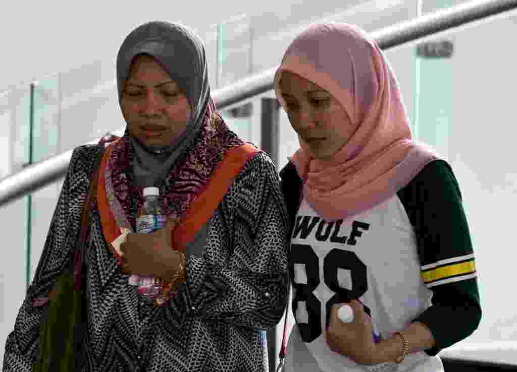 9.mar.2014 - Parentes de um passageiro que estava a bordo do voo MH370 da Malaysia Airlines, que está desaparecido, caminham no hall de um hotel, em Putrajaya, na Malásia, onde familiares estão hospedados enquanto esperam informações sobre o avião desaparecido - Manan Vatsyayana/AFP