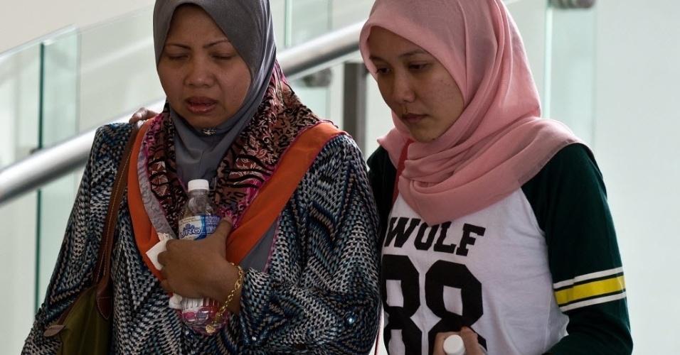 9.mar.2014 - Parentes de um passageiro que estava a bordo do voo MH370 da Malaysia Airlines, que está desaparecido, caminham no hall de um hotel, em Putrajaya, na Malásia, onde familiares estão hospedados enquanto esperam informações sobre o avião desaparecido