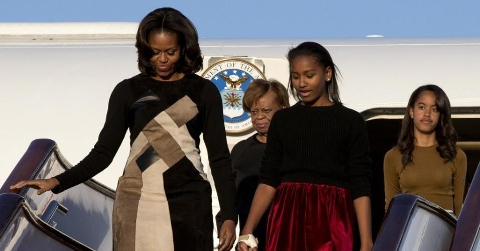 20.mar.2014 - A primeira-dama dos Estados Unidos, Michelle Obama (à esquerda), desembarca no aeroporto internacional de Pequim com sua mãe (2ª à esq.) e suas duas filhas. Michelle fará uma visita de sete dias ao país, onde falará sobre educação e intercâmbio cultural