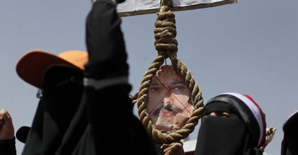 20.mar.2014 - Foto do ex-presidente do Iêmen, Ali Abdullah Saleh, é colocada em corda erguida por uma mulher durante protesto em Sanaa. Os manifestantes exigem a punição dos responsáveis pela morte de pessoas durante protesto antigoverno realizado em março de 2011 na capital do país