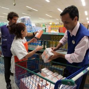Funcionários do Procon retiram leite da marca Elegê das prateleiras de um supermercado de Botafogo, no Rio de Janeiro