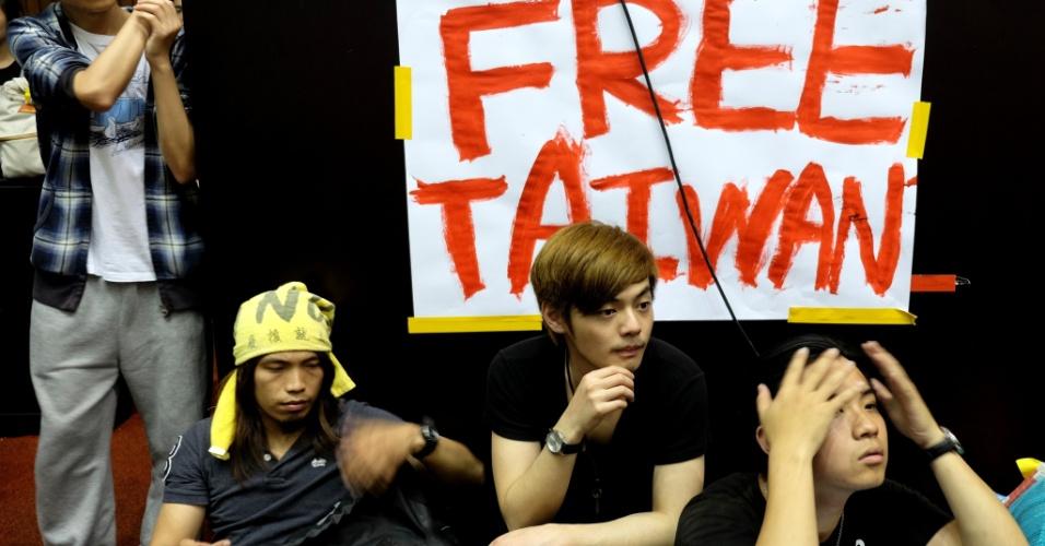 20.mar.2014 - Manifestantes assistem a discurso dentro do Parlamento durante manifestação contra a China realizada em Taipé (Taiwan) nesta quinta-feira (20). Centenas de ativistas foram trancados dentro do parlamento em um impasse com a polícia depois de invadirem o prédio para tentar impedir o governo de ratificar um acordo de comércio com a China